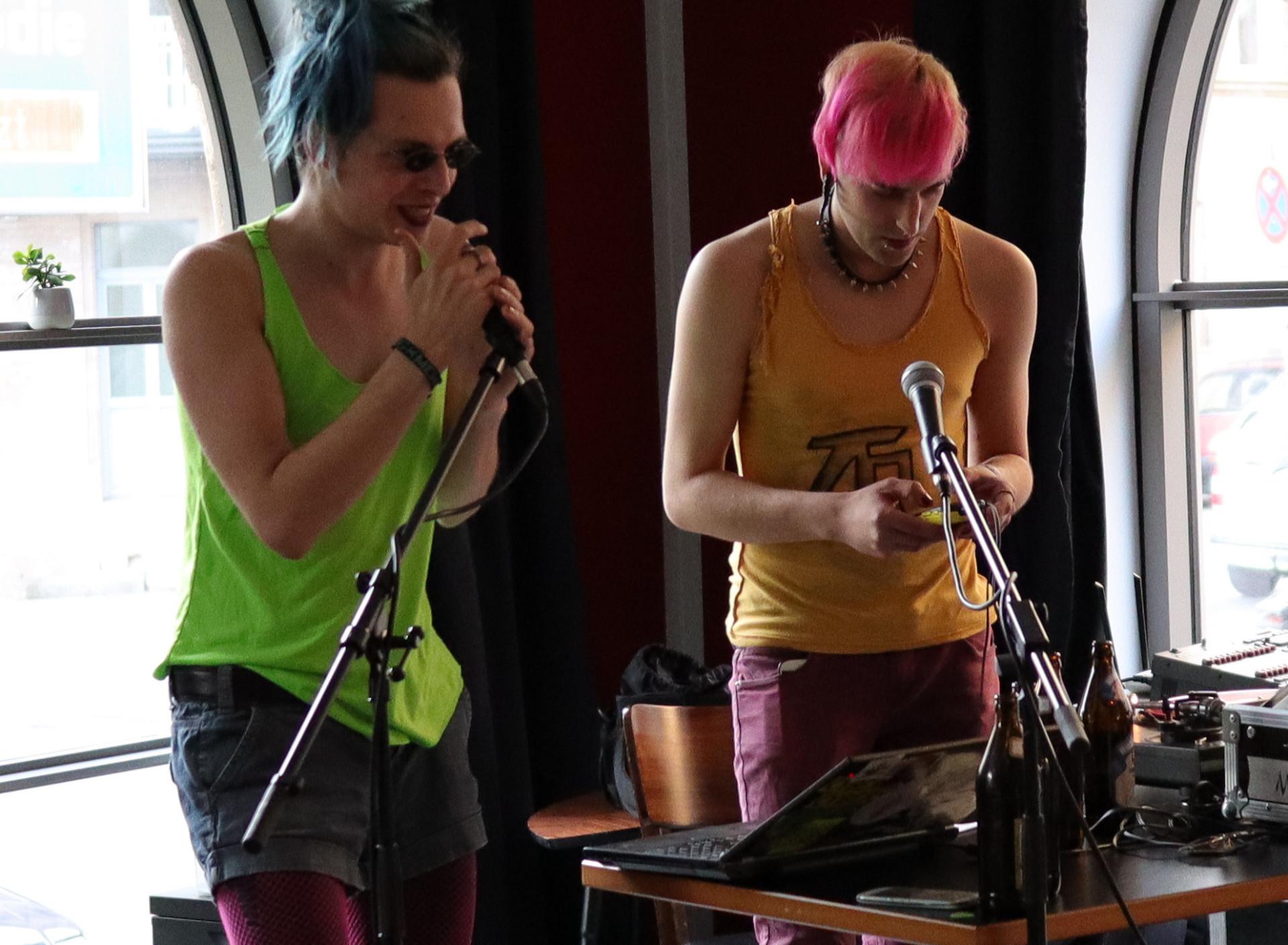 Zwei cyberpunks stehen auf einer Bühne. Einer singt in ein Mikrofon, der andere spielt auf einem Synthesizer.