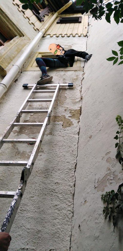 Jemand klettert mit einer langen Leiter durch ein Fenster im ersten Stock des Schlösschens.