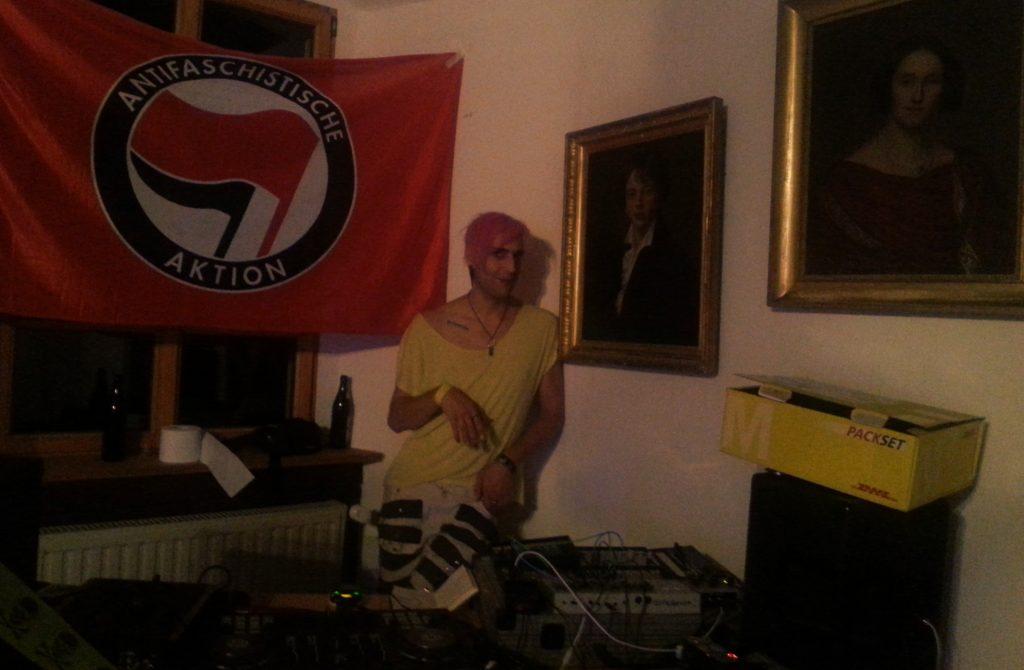 Phant hinter dem DJ-Pult, zwischen Antifa-Fahne und Ahnenportraits.