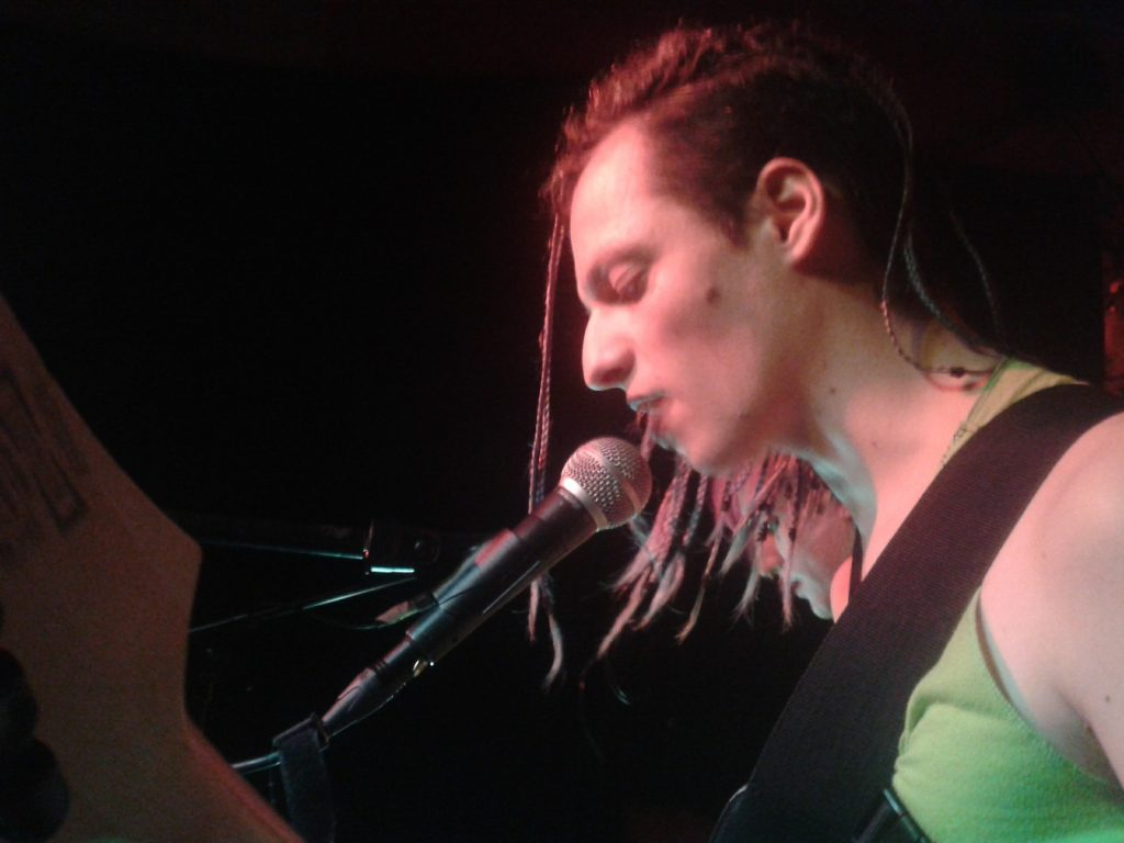 Eine Person im grünen Tanktop und langen Braids singt in ein Mikrofon.