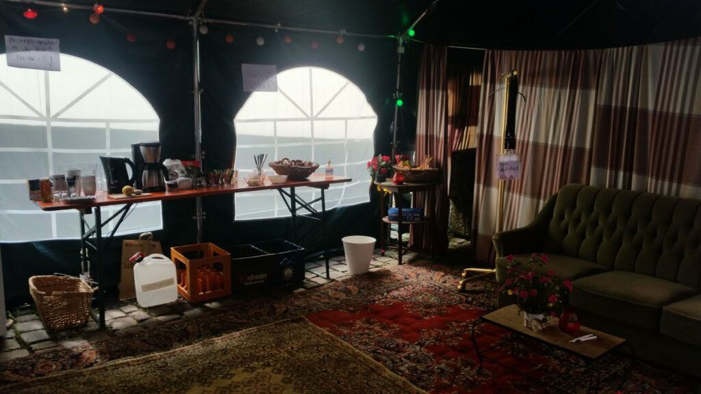 Ein Backstage, auf einem Tisch liegen Snacks, rechts steht ein Sofa, auf dem Boden liegt ein Teppich.