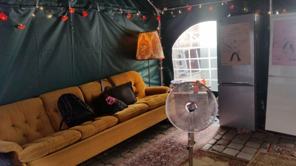 Im Backstage, links steht ein Sofa, rechts ein Getränkekühlschrank. In der Mitte steht ein Ventilator.