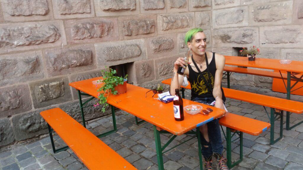 Phant sitzt an einem Tisch, lacht, und trinkt ein alkoholfreies Bier.