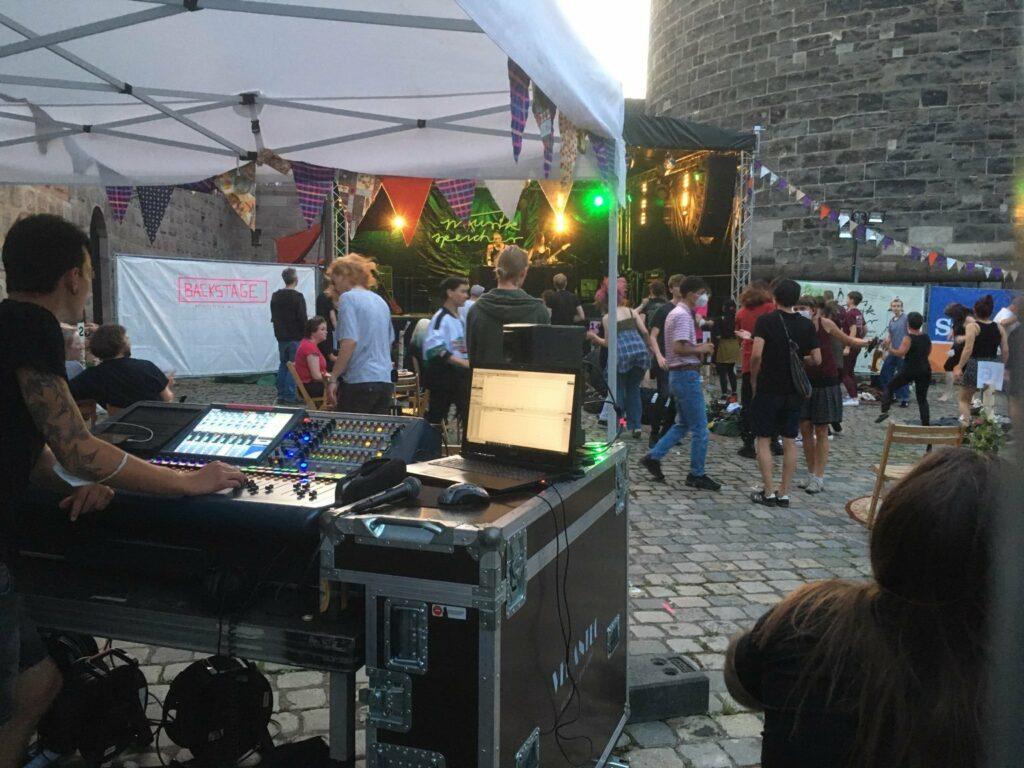 Die Bühne von vorne, es tanzen Leute. Im Vordergrund steht ein Mensch am Mischpult.