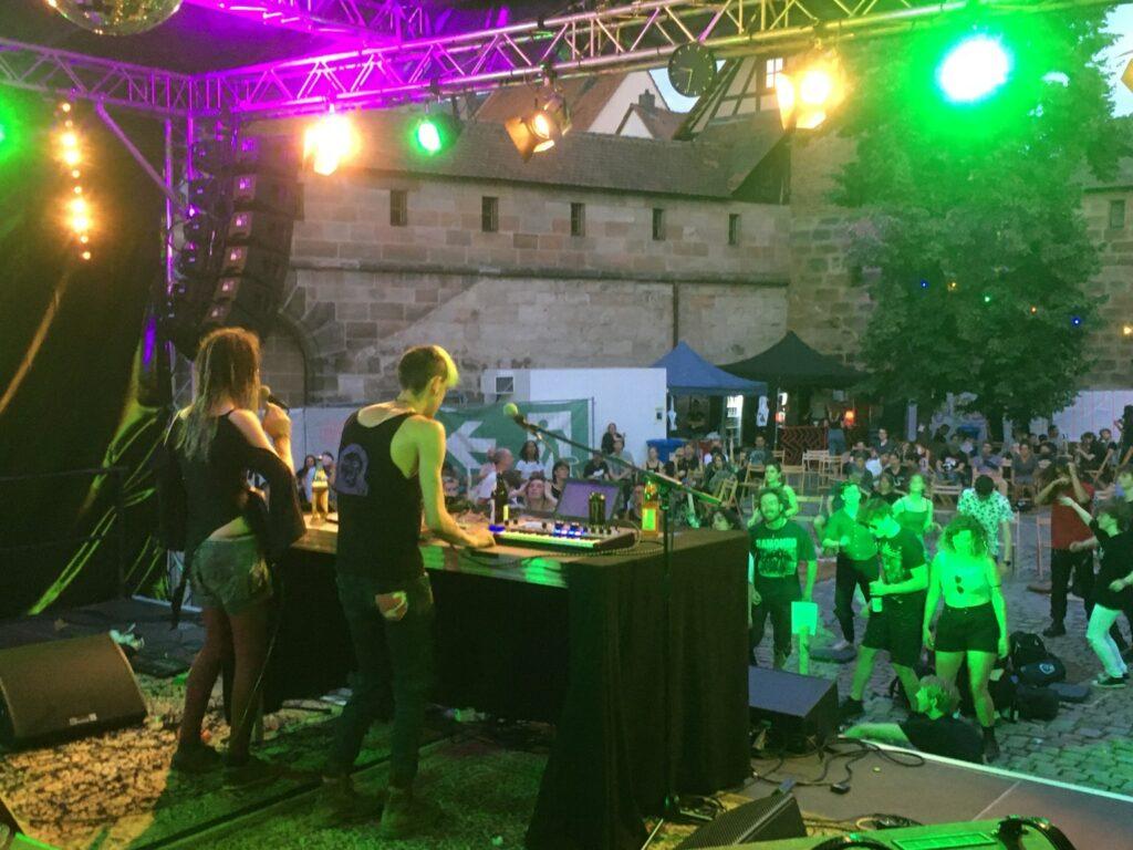 Zwei Cyberpunks stehen auf einer Bühne und machen Musik, davor tanzen Leute.