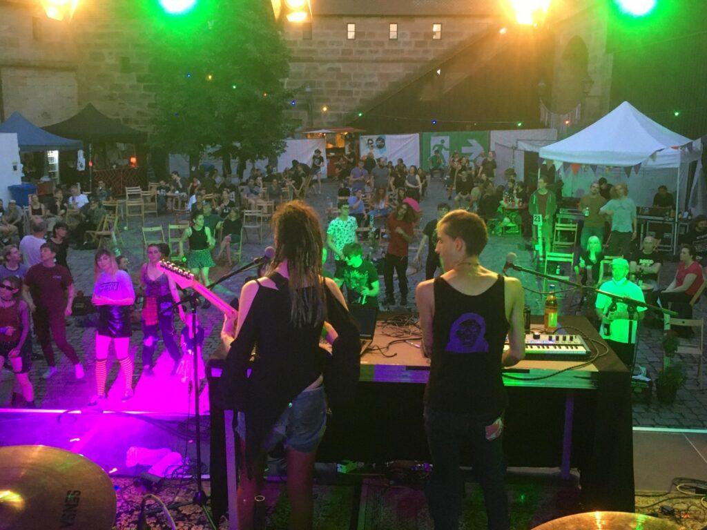 Phant und Nami von hinten, wie sie auf der Bühne stehen und spielen. Vor der Bühne tanzen Leute.